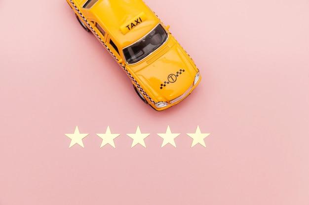 Gelbes spielzeugauto taxi und 5 sterne bewertung lokalisiert auf rosa hintergrund Premium Fotos