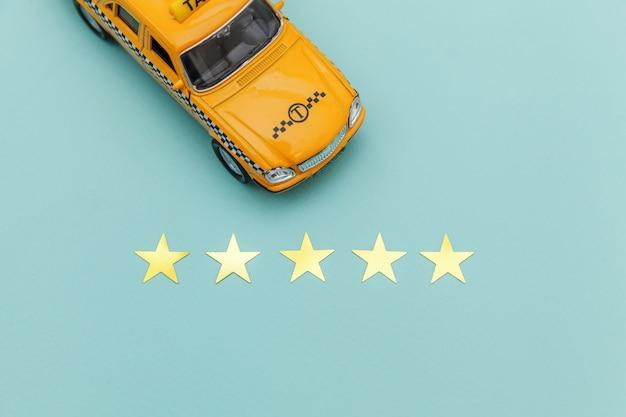 Gelbes spielzeugauto taxi und bewertung mit 5 sternen lokalisiert auf blauem hintergrund. telefonische anwendung von taxi service für online suche telefonieren und buchung cab concept. taxi-symbol. kopieren sie platz. Premium Fotos
