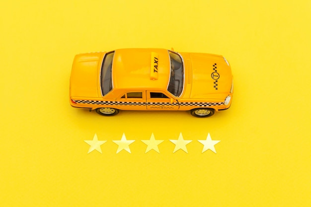 Gelbes spielzeugauto taxi und bewertung mit 5 sternen lokalisiert auf gelbem hintergrund. telefonische anwendung von taxi service für online suche telefonieren und buchung cab concept. taxi-symbol. kopieren sie platz. Premium Fotos