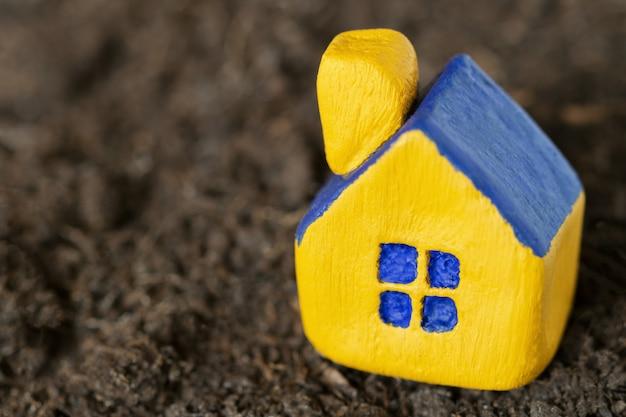 Gelbes spielzeugminiaturhaus mit einem blauen dach auf dunklem boden. tiefenschärfe. Premium Fotos
