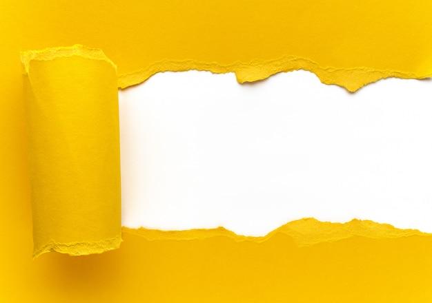 Gelbes zerrissenes papier. quadratisches loch mit weißem hintergrund. Premium Fotos