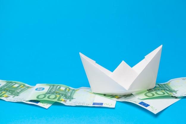 Geld banknoten und papierschiffe. unternehmenskonzept Premium Fotos