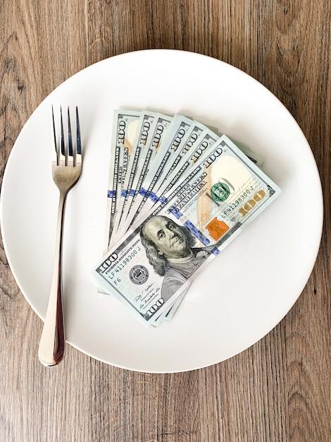 Geld, das auf der platte mit gabel liegt. dollar foto. gieriges korruptionskonzept. bestechungsidee Premium Fotos