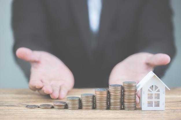 Geld des münzenstapels steigern wachsendes wachstum mit vorbildlichem weißem haus auf holztisch. Premium Fotos