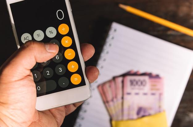 Geld - eine hand mit einem taschenrechner, banknoten, scheinen und mexikanischen pesos Premium Fotos