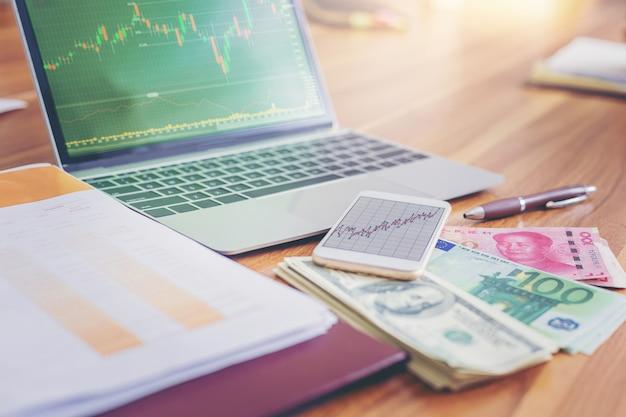Geld usd-dollar, yuan rmb, euro-geld auf laptop mit börse auf dem bildschirm. Premium Fotos