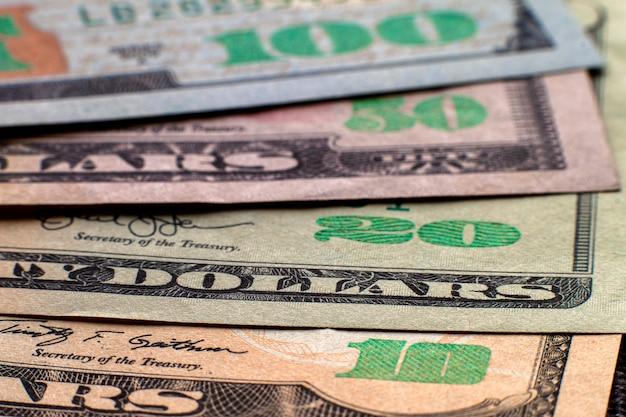 Geld, wohlstand und finanzen. abstraktes licht von amerikanischen usa-landeswährungsbanknoten, details von ordentlich gestapelten rechnungen wert hundert dollar. Premium Fotos