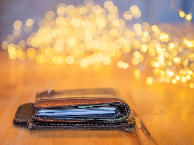 Geldbörse und bewegliches abdeckungsleder auf holztisch mit kleinem verzierendem hellem bokeh hintergrund Kostenlose Fotos