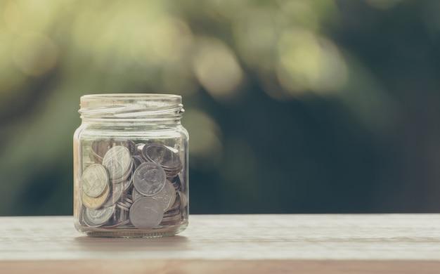 Geldmünze im glasgefäß für einsparungen und finanzinvestitionskonzept Premium Fotos
