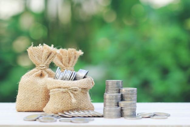 Geldtasche mit stapel münzengeld auf natürlichem grünem hintergrund Premium Fotos