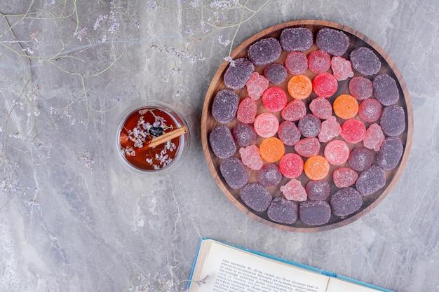 Geleesüßigkeiten in einem holzteller mit einer tasse kräutertee Kostenlose Fotos
