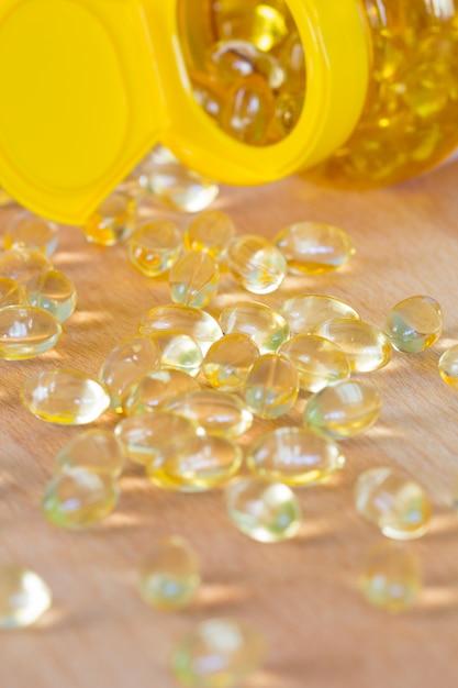 Gelkapseln des lebertrans omega 3 lokalisiert auf hölzernem hintergrund Premium Fotos
