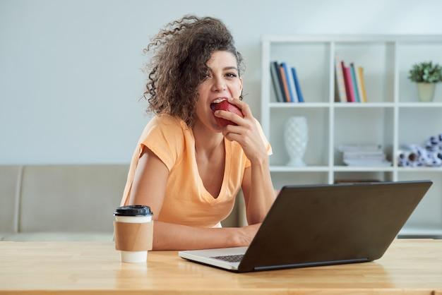 Gelockte junge cauasian frau, die zu hause apfel vor laptop isst Kostenlose Fotos