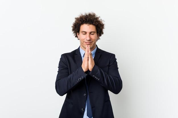 Gelockter mann des jungen geschäfts gegen weißes wandhändchenhalten beten herein nahe mund, glaubt überzeugt. Premium Fotos