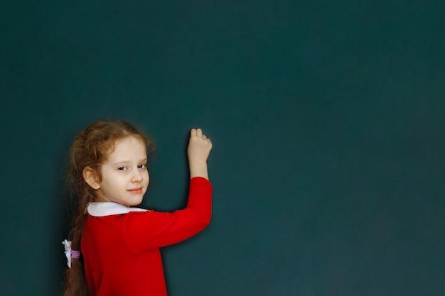 Gelocktes rothaariges mädchen schreibt in kreide steht nahe schulbehörde. Premium Fotos