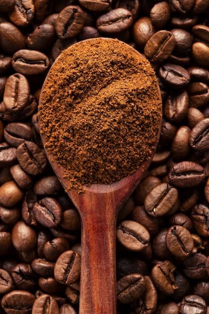 Gemahlener kaffee in einem weinleselöffel auf kaffeebohnen. Premium Fotos