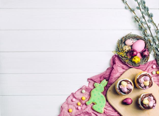 Gemalte eier im natürlichen nest, in den kleinen kuchen und im ingwerbrot auf hellem hölzernem hintergrund Premium Fotos