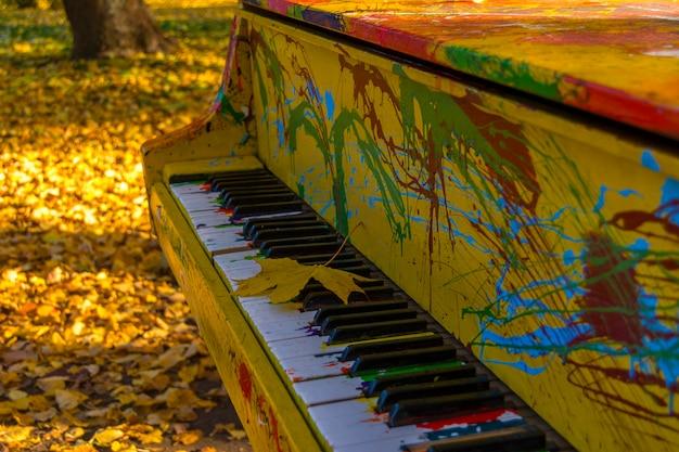 Gemalte farben des klaviers in einem herbstpark. ahornblatt liegt auf den tasten. Premium Fotos