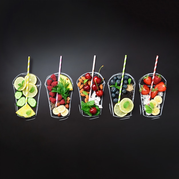 Gemalte gläser mit lebensmittelzutaten für smoothies, getränke auf schwarzer tafel Premium Fotos