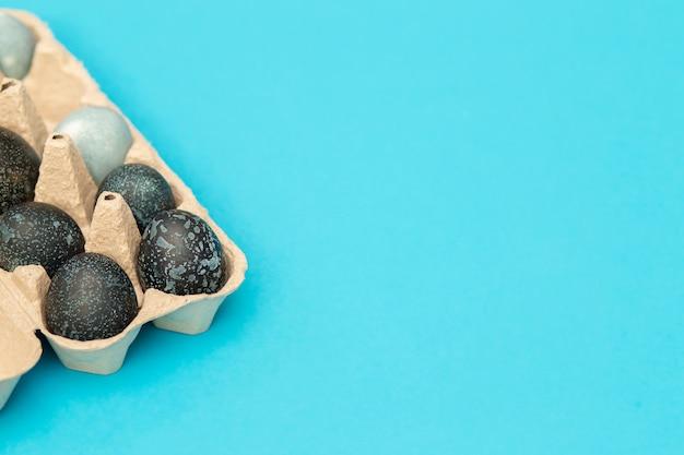 Gemalte ostereier in einer eierbox liegen auf einem blauen hintergrund Premium Fotos