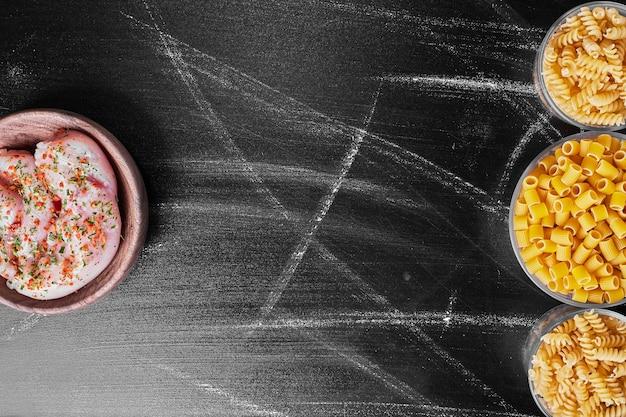 Gemischte nudeln in metallbechern mit rohem hühnerfleisch beiseite. Kostenlose Fotos