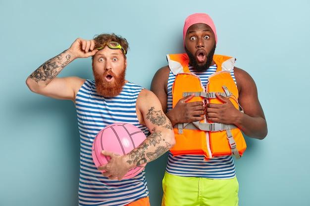 Gemischte rasse zwei männer starren in die kamera Kostenlose Fotos