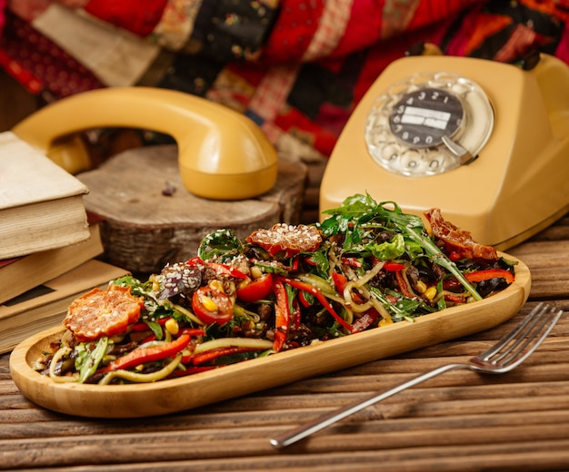 Gemischter gegrillter gemüsesalat mit kräutern und olivenöl in der hölzernen platte mit einem weinlesetelefon herum. Kostenlose Fotos