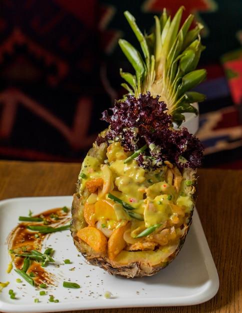 Gemischter obstsalat serviert in geschnitzten ananas mit kräutern. Kostenlose Fotos