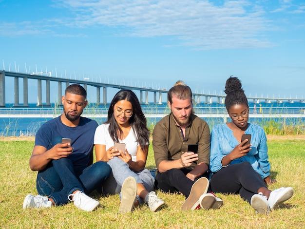 Gemischtrassige freunde, welche die smartphones im freien verwenden Kostenlose Fotos