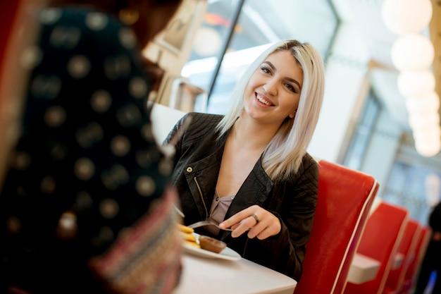 Gemischtrassige freundinnen, die schnellimbiß an einem tisch im restaurant essen Premium Fotos