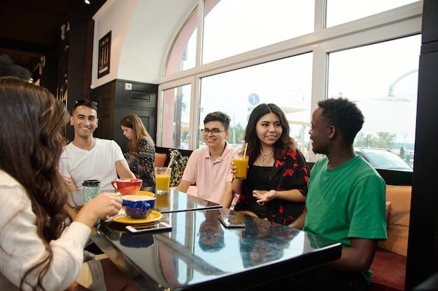 Gemischtrassige glückliche junge leute trinken kaffee im café, fröhliche schwarz-weiß-kumpels lachen und genießen getränke, die spaß am gemeinsamen tisch am restaurant haben, verschiedene freunde teilen sich das mittagessen beim treffen. Premium Fotos