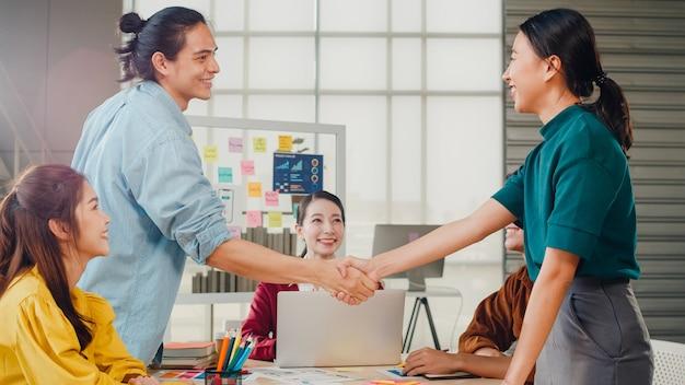 Gemischtrassige gruppe junger kreativer leute in der intelligenten freizeitkleidung, die geschäft, das händeschütteln zusammen und das lächeln während des stehens im modernen büro bespricht. partnerkooperation, mitarbeiter-teamwork-konzept. Kostenlose Fotos