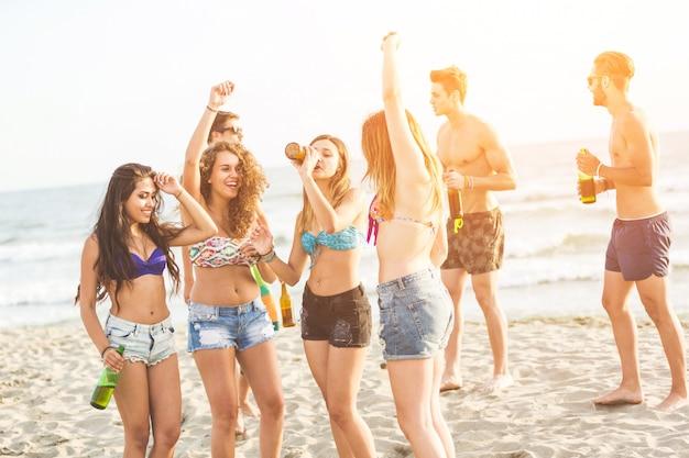 Gemischtrassige gruppe von freunden mit einer party am strand Premium Fotos
