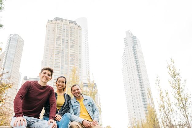 Gemischtrassige lächelnde männer und frau, die zusammen im stadtherbstpark sitzen Kostenlose Fotos