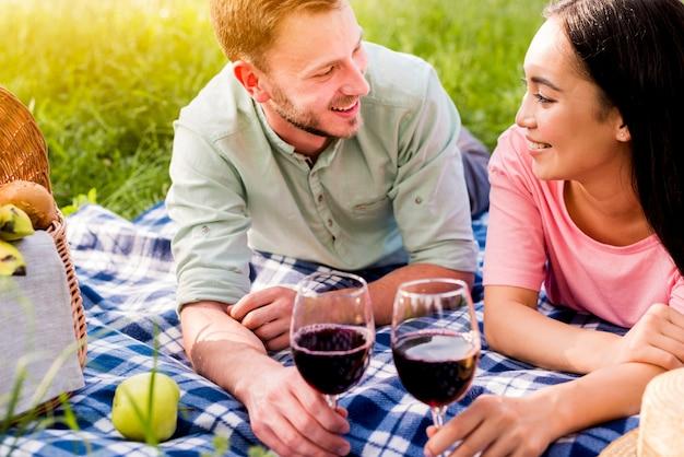 Gemischtrassige lächelnde verliebte paare, die auf kariertem plaid auf picknick liegen Kostenlose Fotos