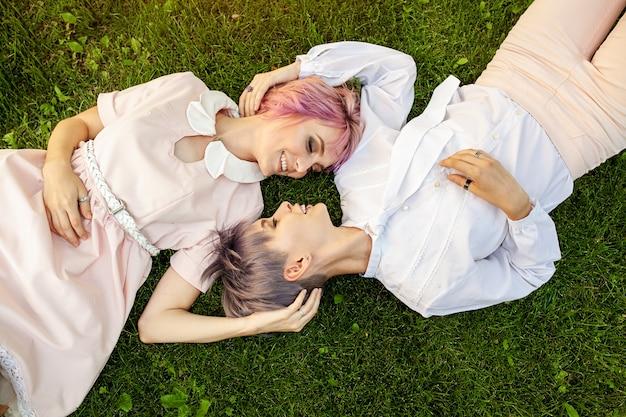 Gemischtrassige lesbische paare, die auf dem gras liegen. Premium Fotos