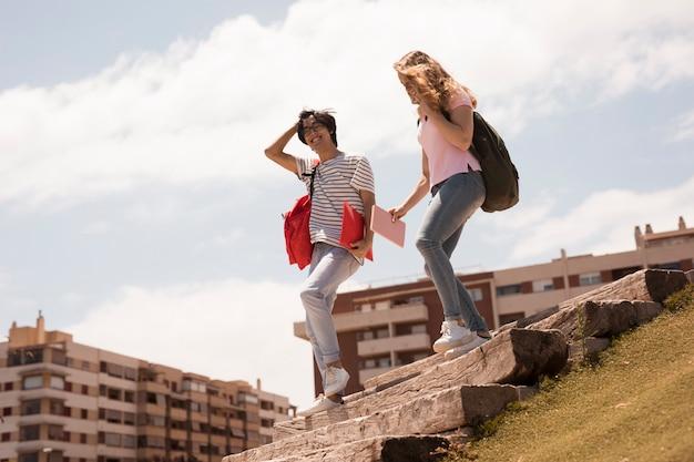 Gemischtrassige nette studenten auf stadttreppen Kostenlose Fotos