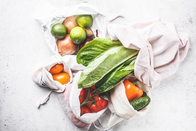 Gemüse in öko-baumwollsäcken, pfeffer, tomaten, salat, gurken, limetten, zwiebeln. kein lebensmitteleinkauf. Premium Fotos