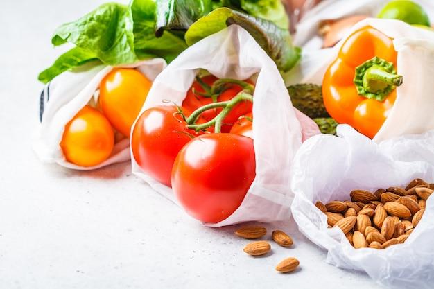 Gemüse in öko-baumwollsäcken, pfeffer, tomaten, salat, gurken, limetten, zwiebeln und nüssen. Premium Fotos