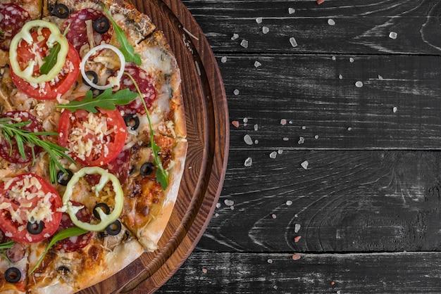 Gemüse-, pilz- und tomatenpizza auf einem schwarzen hölzernen hintergrund. Premium Fotos