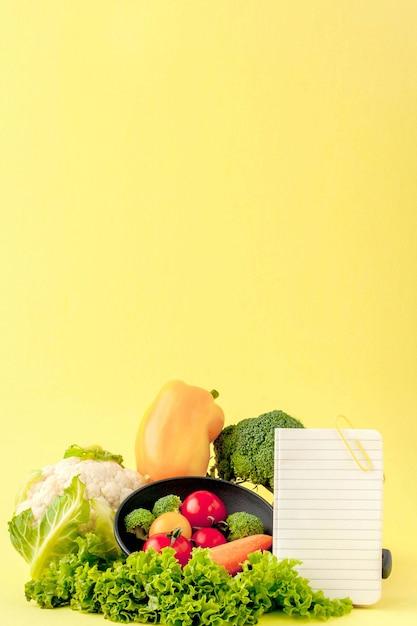 Gemüse und notizbuch mit kopienraum auf gelbem hintergrund Premium Fotos