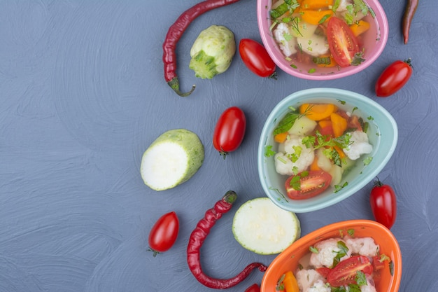 Gemüsebrühe suppe in bunten tassen auf blau. Kostenlose Fotos