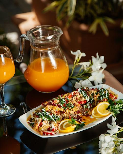 Gemüseeintopf, garniert mit kräutern und zitrone, serviert mit orangensaft Kostenlose Fotos