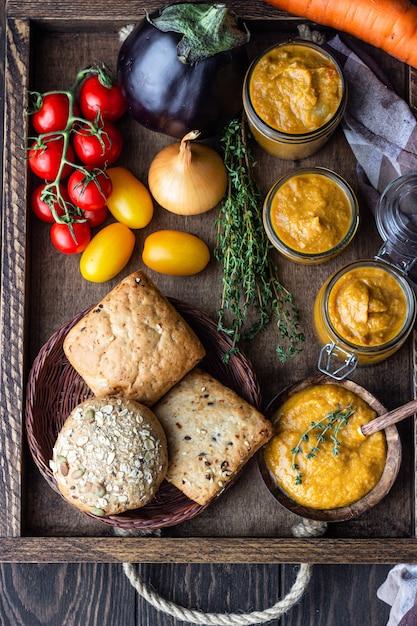 Gemüsekaviar in gläsern, frischen tomaten, zwiebeln, karotten, auberginen und thymian serviert mit brot in einem holztablett. hausgemachte konfitüren. vegane küche. herbsternte. Premium Fotos