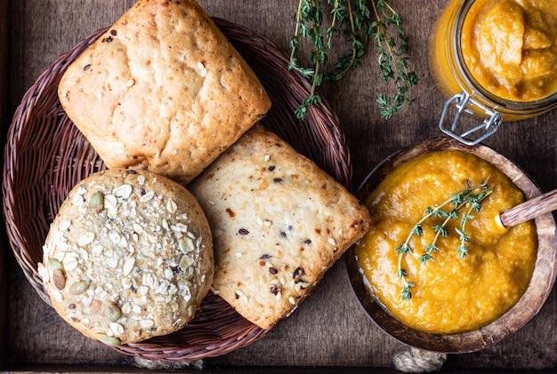 Gemüsekaviar in gläsern, frischen tomaten, zwiebeln, karotten, auberginen und thymian serviert mit brot in einem holztablett. Premium Fotos