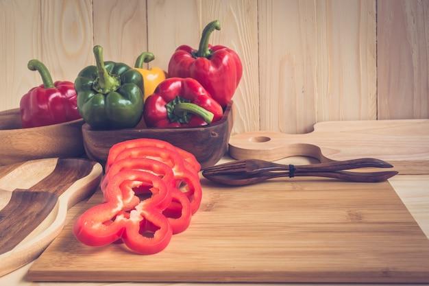 Gemüsepaprikas auf holztischhintergrund Premium Fotos