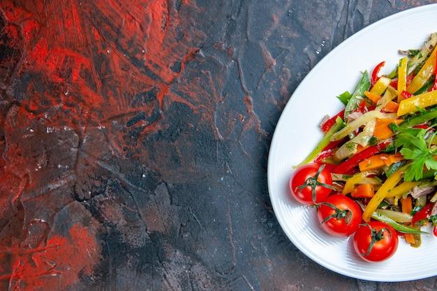Gemüsesalat der oberen hälfte auf ovalem teller auf dunkelrotem oberflächenfreiraum Kostenlose Fotos