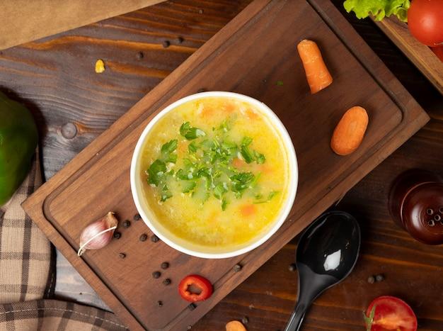 Gemüsesuppe der hühnerbrühe in der wegwerfschalenschüssel diente mit grünem gemüse. Kostenlose Fotos