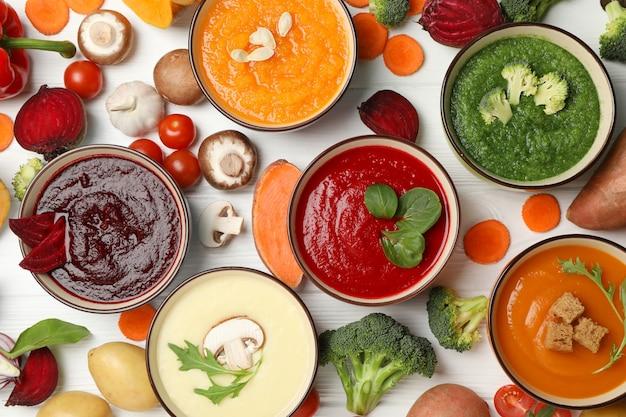 Gemüsesuppen und zutaten auf weißem holz, draufsicht Premium Fotos