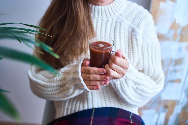 Gemütliche frau im gestrickten weißen pullover, der ein glas des süßen wärmenden kakaos hält. heiße getränke Premium Fotos